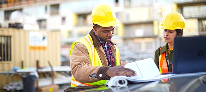 engineers reviewing blueprints of construction plan